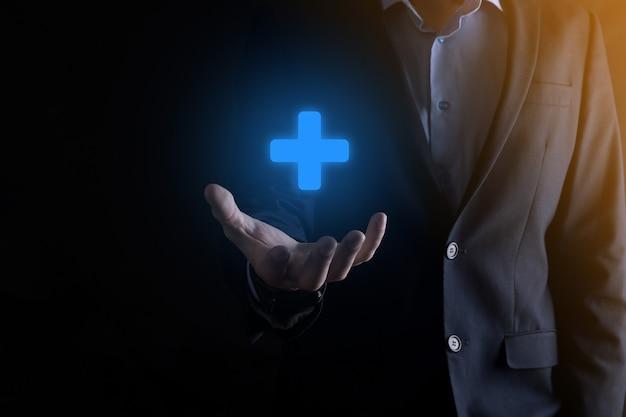 Homme d'affaires, l'homme en main offre des choses positives telles que le profit, les avantages, le développement, la rse représentée par le signe plus.la main montre le signe plus.