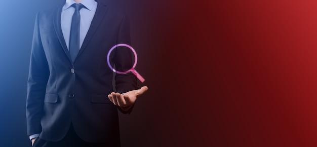Homme d'affaires, homme tenir dans la main l'icône de la loupe. concept d'entreprise, de technologie et d'internet