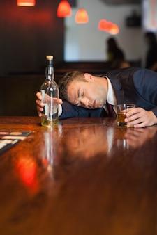 Homme d'affaires immobile tenant le verre de whisky allongé sur un comptoir