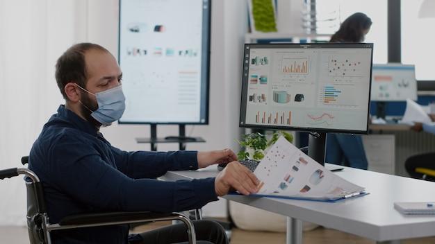 Homme d'affaires immobilisé avec masque de protection travaillant dans une nouvelle société financière commerciale normale tapant ...