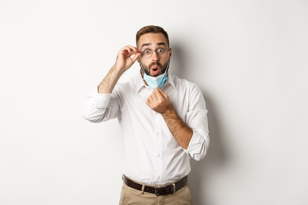 Homme d'affaires impressionné décoller le masque médical, à la surprise, debout