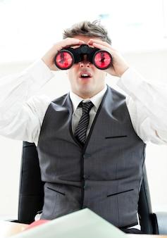 Homme d'affaires impressionné regardant à travers des jumelles assis dans son bureau