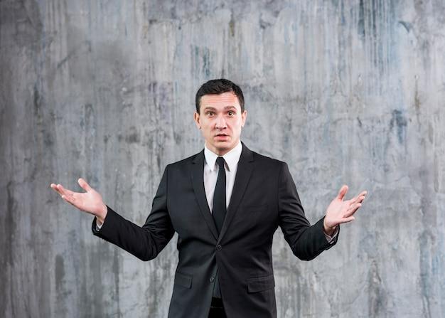 Homme d'affaires incompris debout avec les mains levées