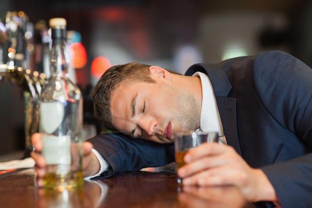 Homme d'affaires inconscient tenant le verre de whisky allongé sur un comptoir