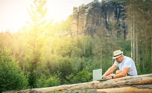 Homme d'affaires indépendant avec succès avec un ordinateur portable dans les montagnes