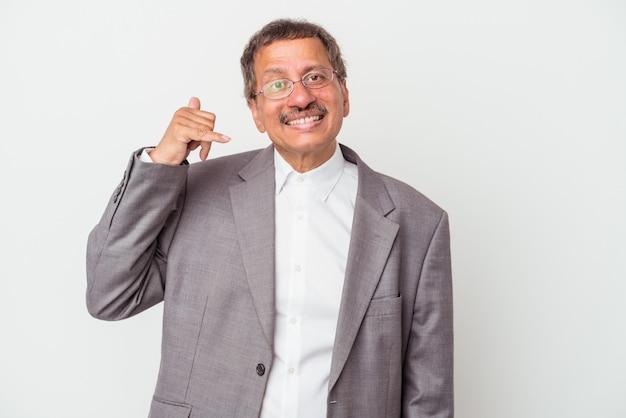 Homme d'affaires indien d'âge moyen isolé sur fond blanc montrant un geste d'appel de téléphone portable avec les doigts.