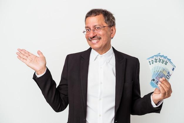 Homme d'affaires indien d'âge moyen tenant des factures isolées sur fond blanc montrant un espace de copie sur une paume et tenant une autre main sur la taille.