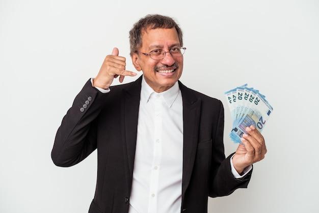 Homme d'affaires indien d'âge moyen tenant des factures isolées sur fond blanc montrant un geste d'appel de téléphone portable avec les doigts.