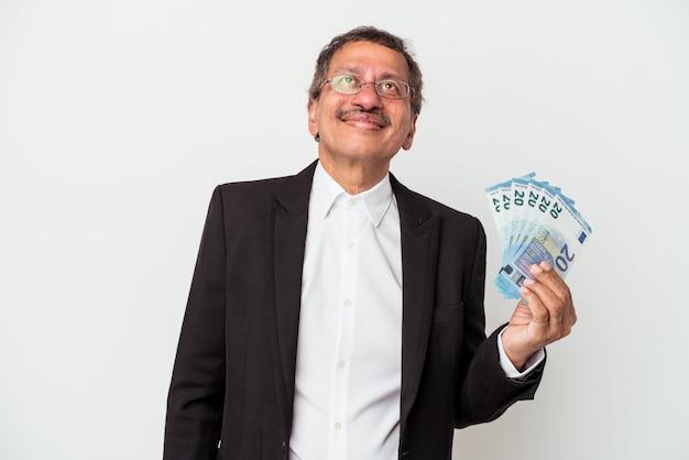 Homme d'affaires indien d'âge moyen tenant des factures isolées sur fond blanc rêvant d'atteindre des objectifs et des objectifs