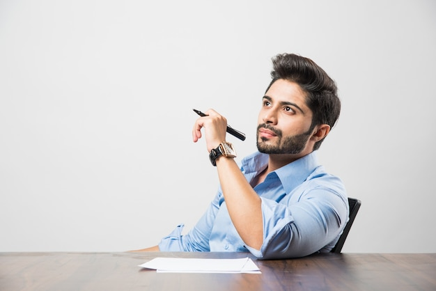 Homme d'affaires indien écrivant un document alors qu'il était assis au bureau ou au poste de travail