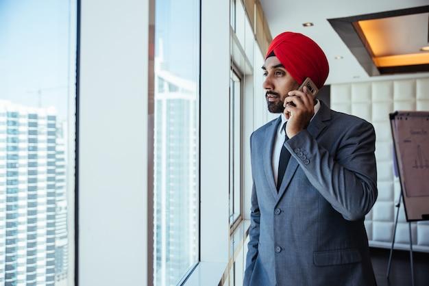 Homme d'affaires indien regardant par la fenêtre dans son bureau