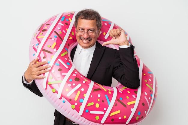 Un homme d'affaires indien senior tenant un beignet gonflable isolé sur fond blanc se sent fier et confiant, exemple à suivre.