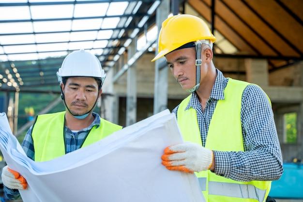 Homme d'affaires et ingénieur en construction travaillant avec un plan sur le chantier de construction.