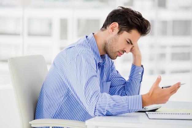 Homme d'affaires inquiet, calcul des comptes sur une calculatrice