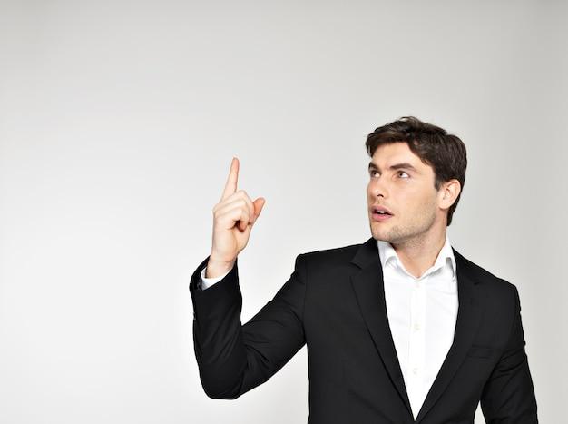 Homme d'affaires d'inspiration heureuse pointe son doigt en costume noir
