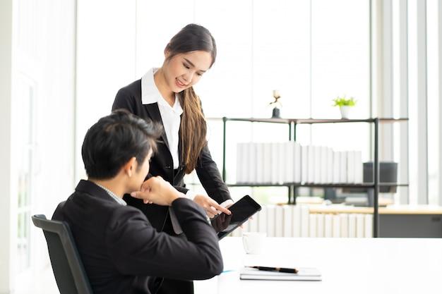 Homme d'affaires intelligent asiatique et femme d'affaires parler ensemble dans la salle de réunion