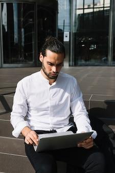 Homme d'affaires intelligent assis sur l'escalier à l'aide d'un ordinateur portable