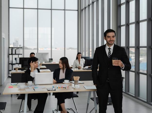 Homme d'affaires intelligent et attrayant tenant un café et impatient de travailler avec des personnes travaillant, le succès de l'équipe commerciale, l'analyse et le concept de stratégie
