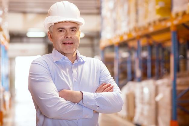 Homme d'affaires intelligent confiant souriant tout en travaillant dans son entrepôt