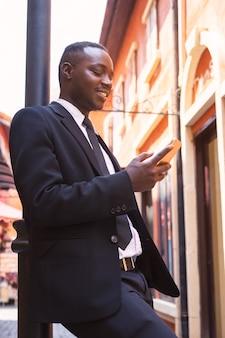 Homme d'affaires intelligent debout et à l'aide de smartphone dans la ville