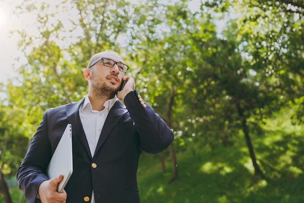 Homme d'affaires intelligent réussi en chemise blanche, costume classique, lunettes. l'homme se tient debout avec un ordinateur portable, parle sur un téléphone portable dans le parc de la ville à l'extérieur sur fond de nature. bureau mobile, concept d'entreprise.