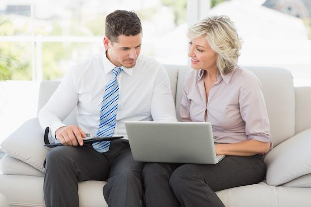 Homme d'affaires intelligent et sa secrétaire avec agenda et ordinateur portable