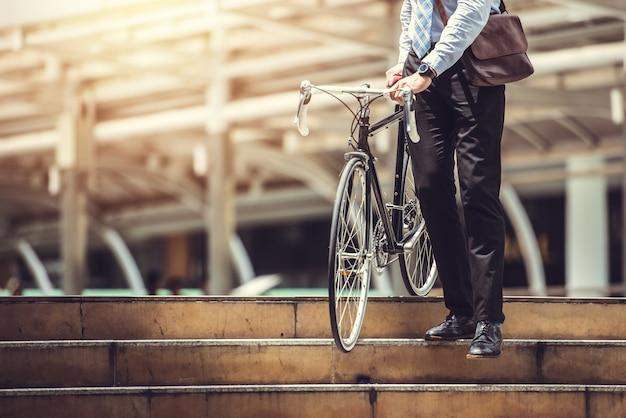 Homme d'affaires intelligent tenant un vélo goto travaux sur le trottoir urbain en heure de pointe - concept écologique et de modes de vie