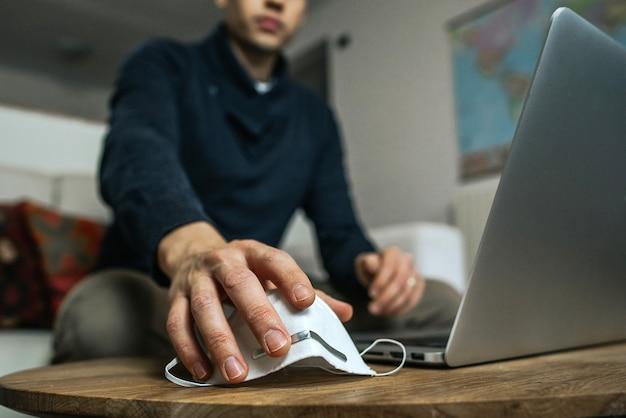 Homme d & # 39; affaires intelligent travaillant sur un ordinateur portable à la maison en prenant un masque de protection contre les coronavirus