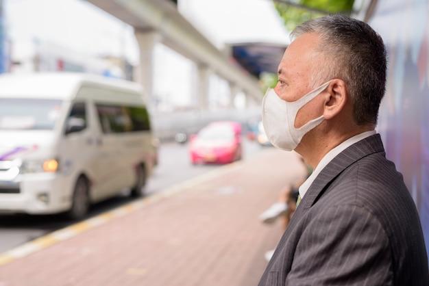 Homme d'affaires japonais mature avec masque assis avec distance à l'arrêt de bus