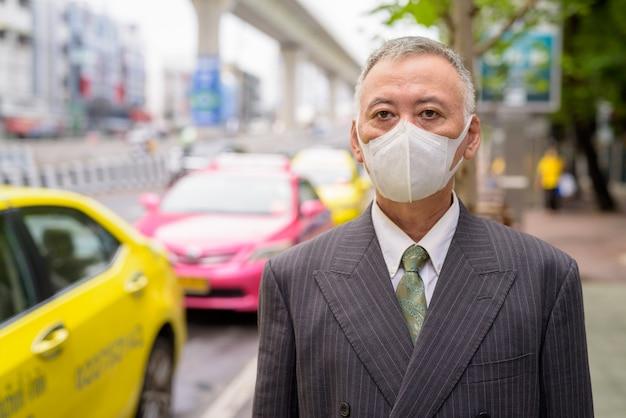 Homme d'affaires japonais mature avec masque en attente à la station de taxi