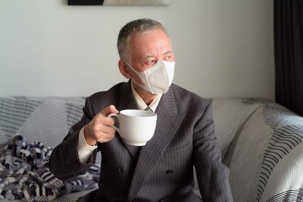 Homme d'affaires japonais mature avec masque restant à la maison en quarantaine