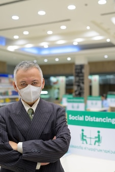 Homme d'affaires japonais mature avec masque social distanciation à l'aire de restauration