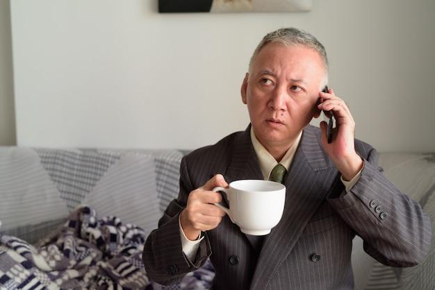 Homme d'affaires japonais mature, parler au téléphone et tenant du café à la maison