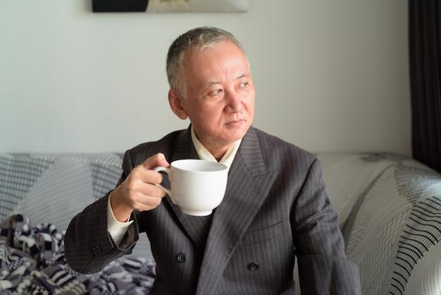 Homme d'affaires japonais mature pensant tout en buvant du café à la maison