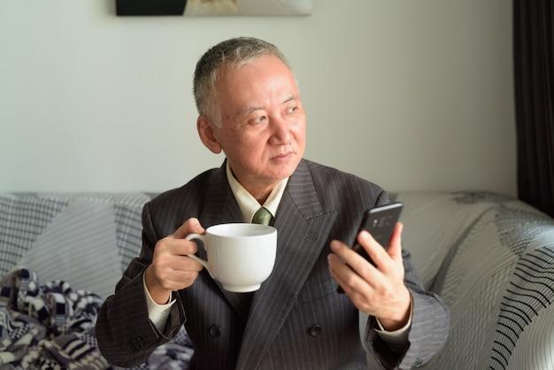 Homme d'affaires japonais mature pensant tout en tenant le téléphone et le café à la maison