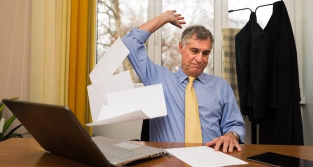 Homme d'affaires jetant des feuilles de papier dans son bureau