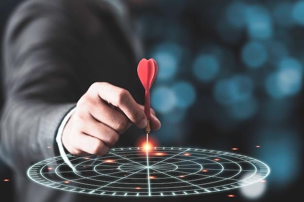Homme d & # 39; affaires jetant une flèche rouge sur un jeu de fléchettes cible virtuelle