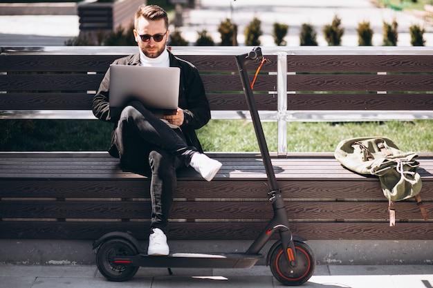 Homme d'affaires jeune assis sur le banc et travaillant sur ordinateur