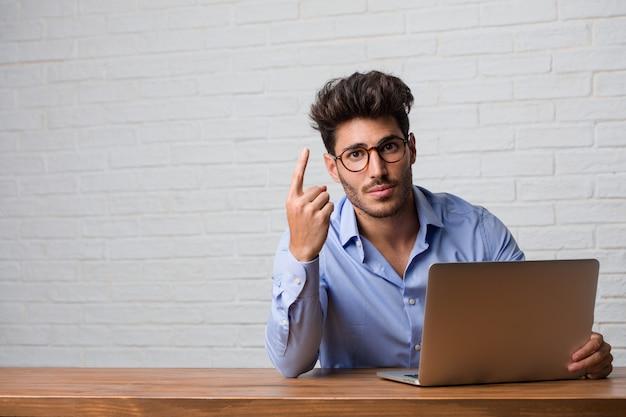 Homme d'affaires jeune assis et travaillant sur un ordinateur portable montrant le numéro un, symbole de comptage