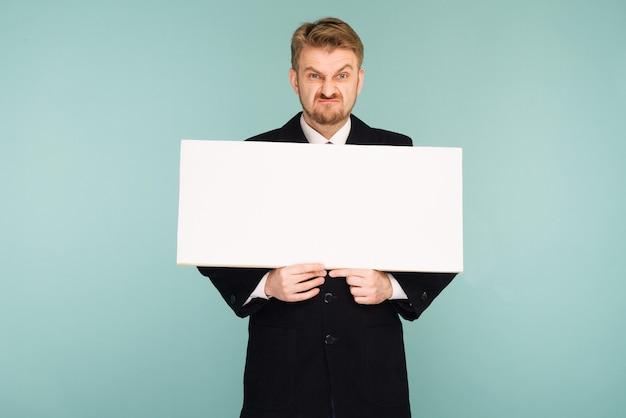 Homme d'affaires jeune barbe en colère montrant une pancarte vierge, sur bleu