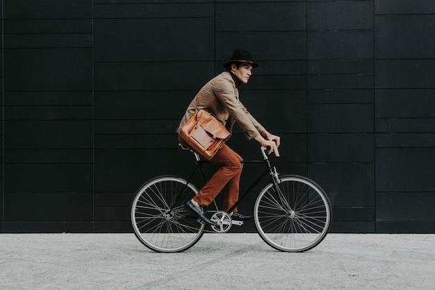 Homme d'affaires jeune beau avec son vélo moderne.
