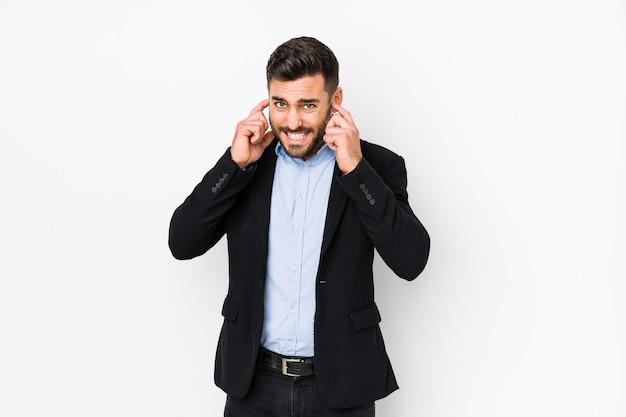 Homme d'affaires jeune caucasien sur blanc isolé couvrant les oreilles avec les mains.