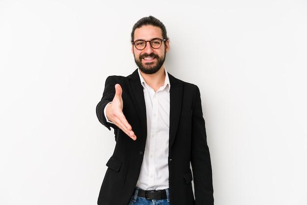 Homme d'affaires jeune caucasien isolé sur une main blanche qui s'étend à la caméra en geste de salutation.