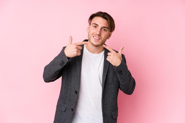 Homme d'affaires jeune caucasien posant des sourires isolés, pointant du doigt la bouche.