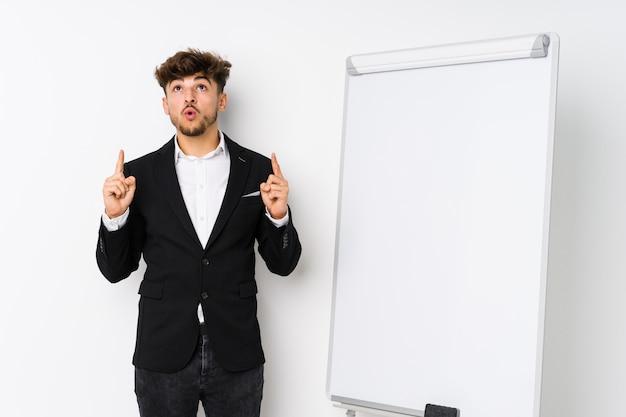 Homme d'affaires jeune coaching pointant à l'envers avec la bouche ouverte