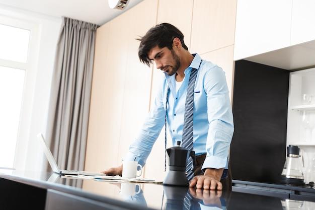 Homme d'affaires jeune concentré à la cuisine, parler par téléphone mobile.
