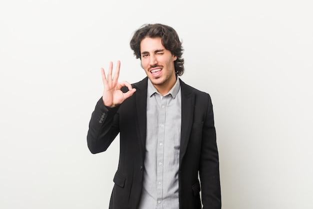 Homme d'affaires jeune contre un mur blanc clignote un œil et tient un geste correct avec la main.