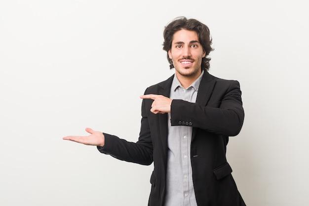 Homme d'affaires jeune contre un mur blanc excité tenant un espace de copie sur la paume.