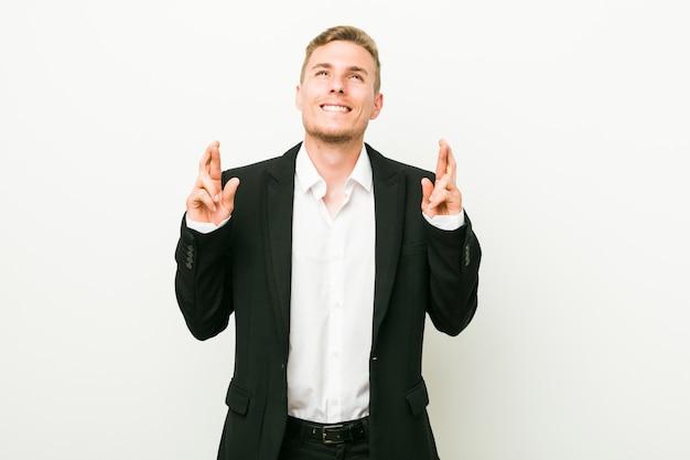 Homme d'affaires jeune croise les doigts pour avoir de la chance
