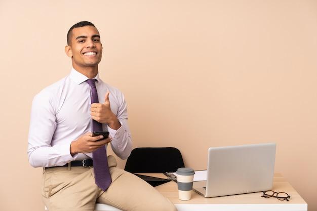 Homme d'affaires jeune dans un bureau donnant un coup de pouce geste